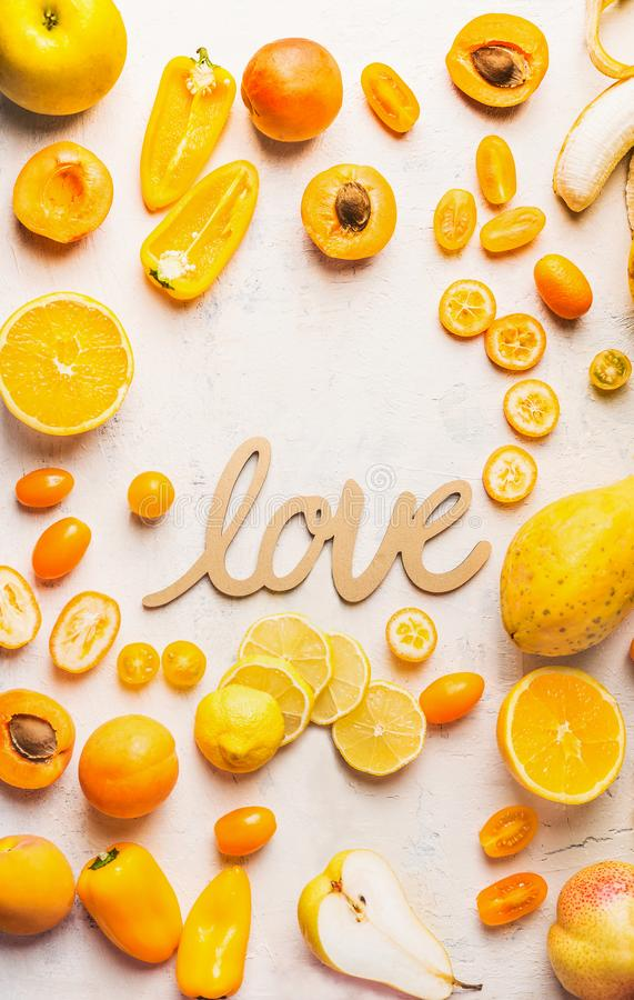 Various yellow and orange color fruits and vegetables on white table background with word love sign. Flat lay. Food layout. Color royalty free stock photos