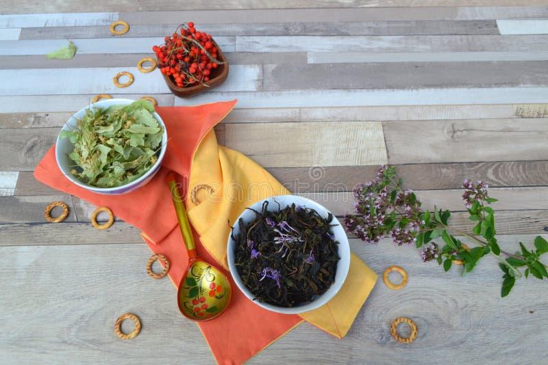 Varius herbal tea, russian cuisine: linden tea, mint, ivan tea blooming sally and rowan berries. Rusticwooden shabby table royalty free stock photo