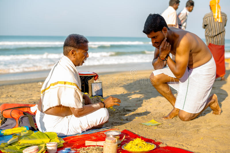 Varkala, India - February 22, 2013: Hindu Brahmin with religious. Attributes providing ceremony and are blessing pilgrim in the morning. Varkala beach, Kerala royalty free stock images