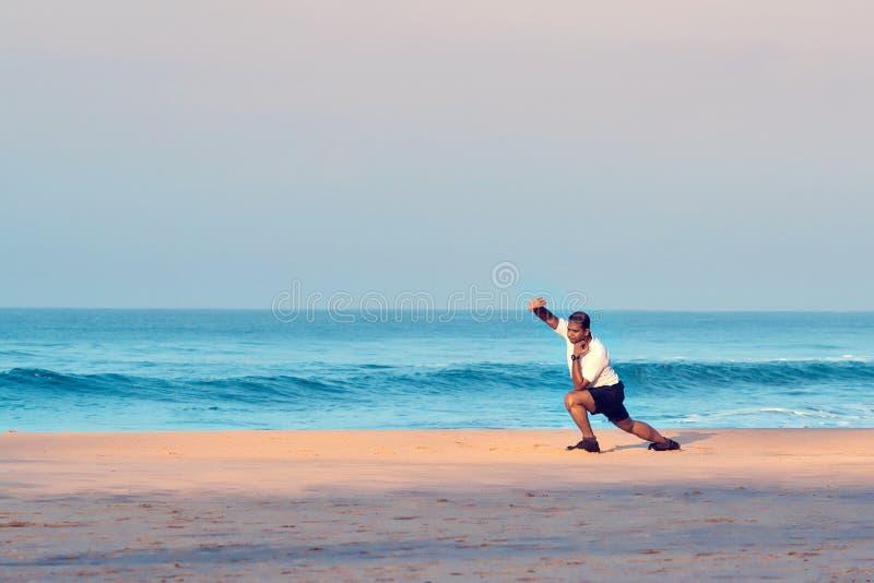 Varkala, Kerala, Indien - 30. November 2017: Indischer Mann, der Morgenyogaasana und -körperliche Bewegungen auf dem Strand tut stockfotos