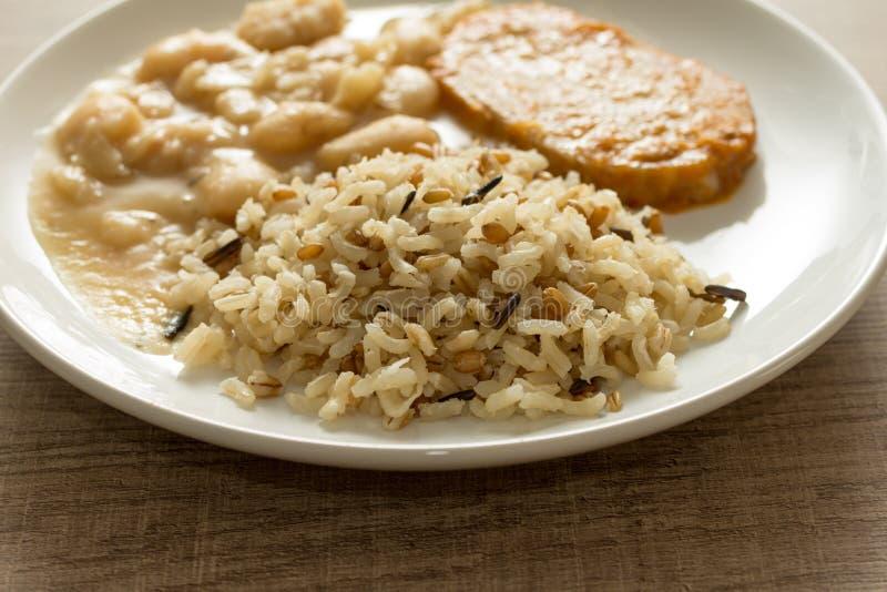 Varkenskotelet, ongepelde rijst en witte bonen Witte schotel op houten tabl royalty-vrije stock afbeelding