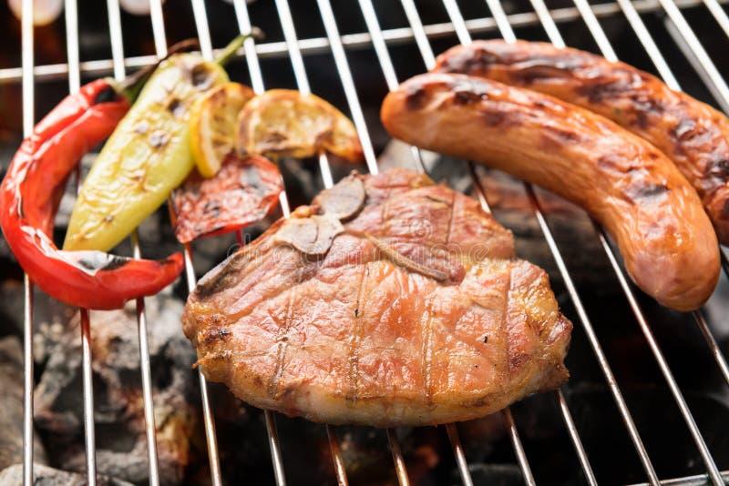 Varkenskoteletlapje vlees en groente met worst op vlammende BBQ gril stock fotografie