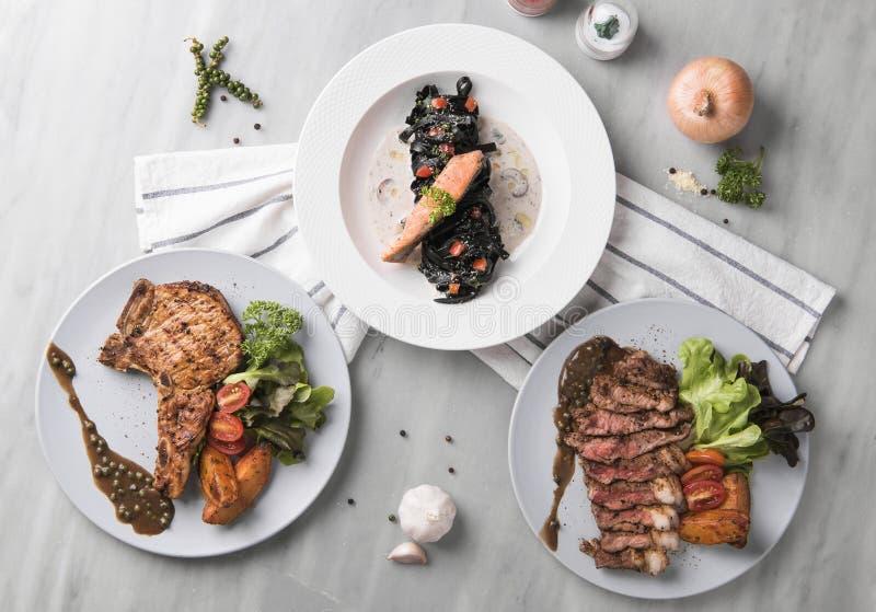 Varkenskoteletlapje vlees met rundvleeslapje vlees en zalm zwarte deegwaren royalty-vrije stock foto