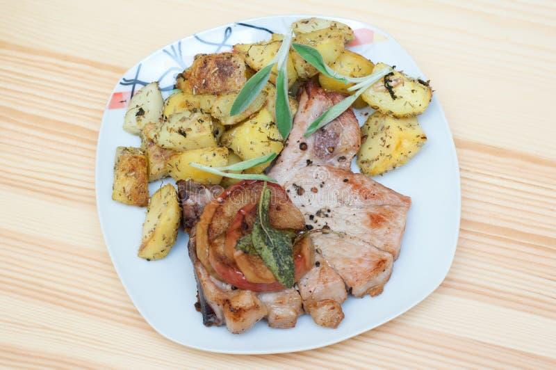 Varkenskoteletten met appelen en aardappels stock afbeelding