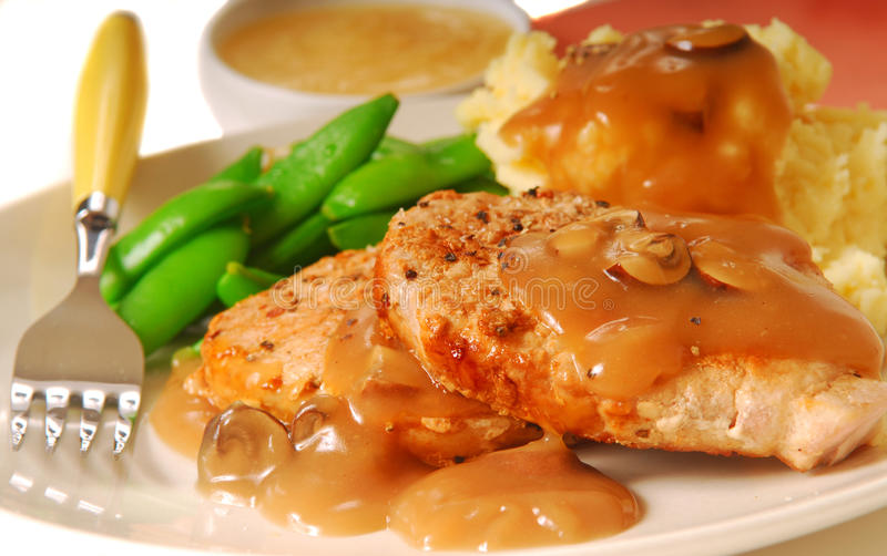 Varkenskoteletten met bonen en fijngestampte aardappels stock foto