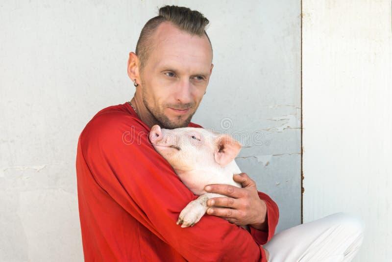 Varkenslandbouwer met leuk biggetje in handen bij landbouwbedrijfmuur Nadruk op piggy royalty-vrije stock afbeelding