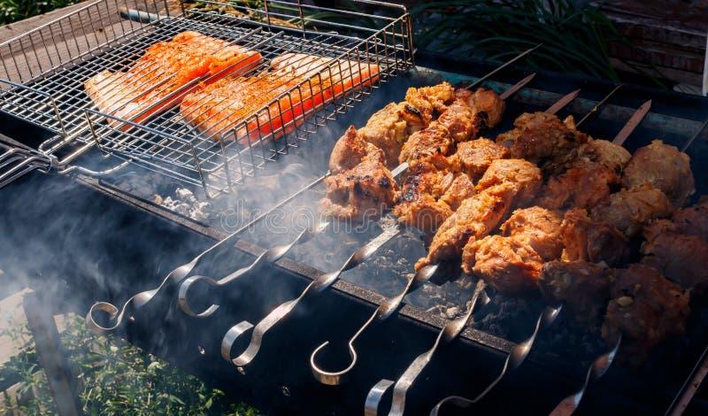 Varkensvlees en zalmkebabs die buiten roosteren royalty-vrije stock fotografie