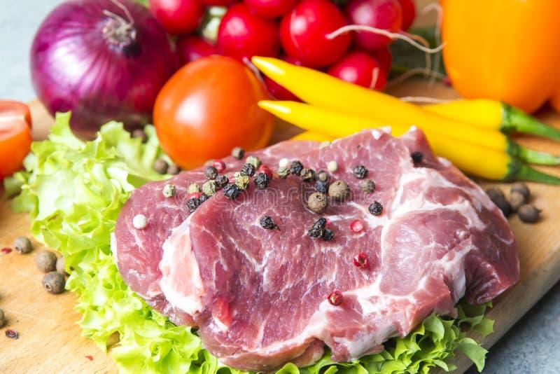 Varkensvlees-hals vleeslapjes vlees op sla op de achtergrond van radijzen, tomaat, rode Spaanse peperpeper, gele Spaanse peperpep stock fotografie
