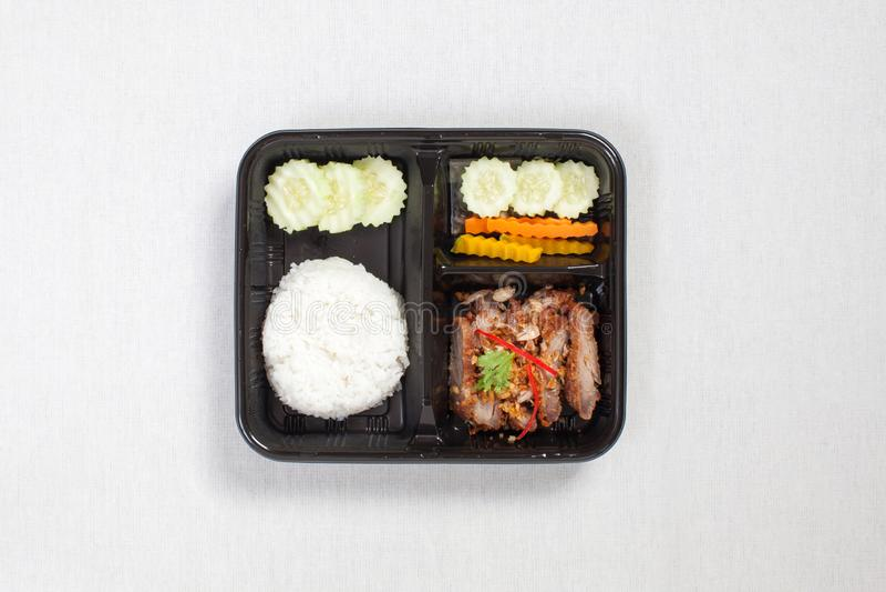 Varkensvlees met knoflook en peper en rijst, verpakt in een zwarte plastic doos, op een witte tafellade, in een doos met levensmi stock afbeeldingen