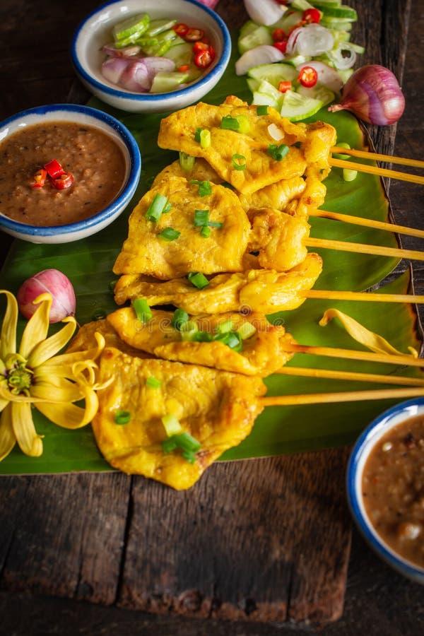Varkensvlees satay met Thaise die kruiden en pindasaus op banaanblad op de houten lijst wordt geplaatst stock afbeeldingen