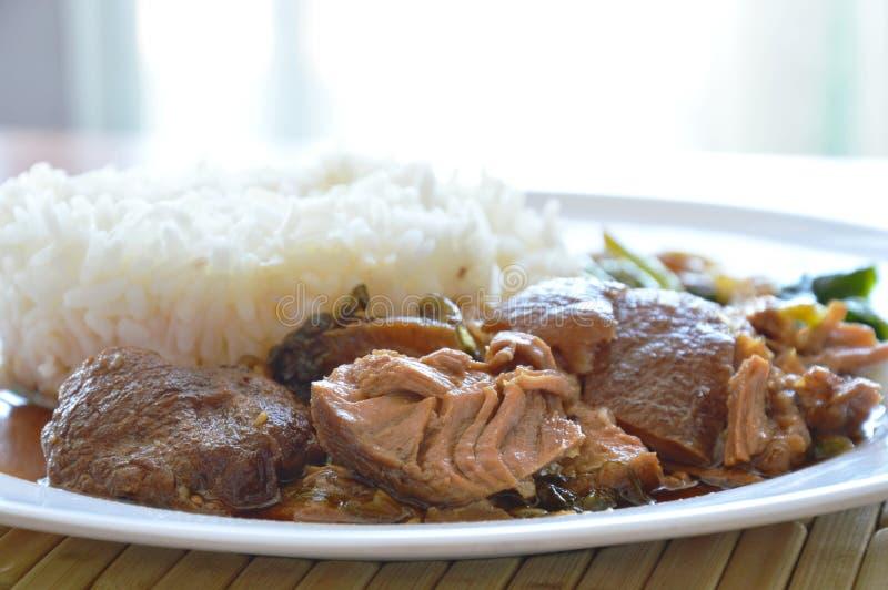 Varkensvleesbeen dat met rijst op plaat wordt gestoofd stock afbeelding