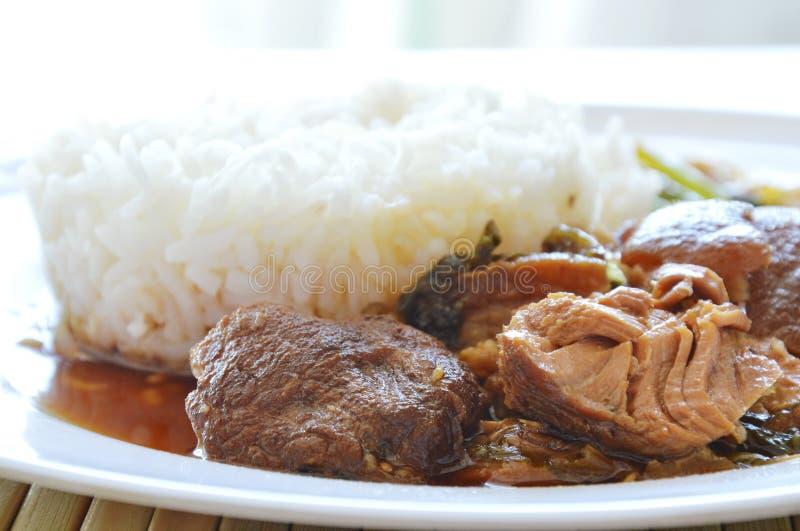 Varkensvleesbeen dat met rijst op plaat wordt gestoofd stock foto