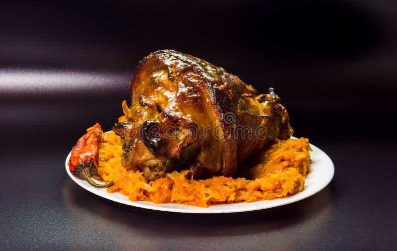 Varkensvleesbeen voor diner Heerlijk voedsel op een donkere achtergrond royalty-vrije stock afbeeldingen