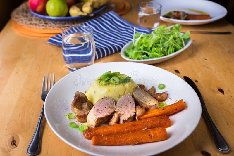 Varkensvleeshaasbiefstuk, fijngestampte aardappel en wortel op plaat, salade op houten lijst stock foto