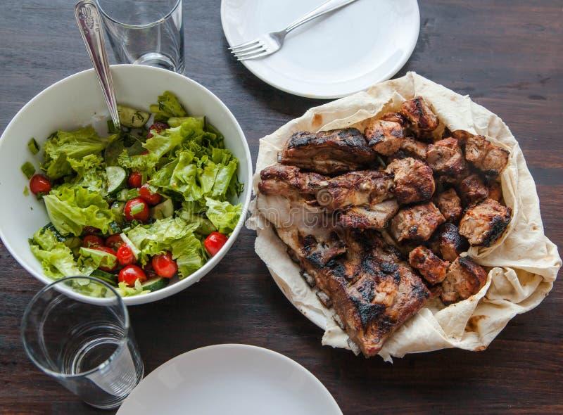 Varkensvleeshals, op houtskool, close-up wordt gekookt dat Varkensvleeshals van houtskool, plantaardige salade wordt gemaakt die royalty-vrije stock foto