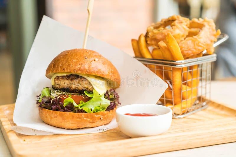 varkensvleeshamburger met uiringen en frieten royalty-vrije stock afbeelding