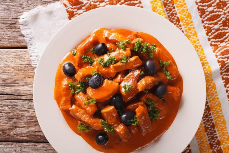 Varkensvleeshutspot in een kruidige saus van wijn, tomaten en room met oliv royalty-vrije stock foto's