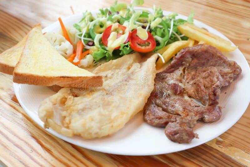 Varkensvleeslapje vlees en vissenlapje vlees met salade en gebraden gerechten stock afbeeldingen