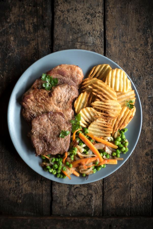 Varkensvleeslapje vlees met chips royalty-vrije stock afbeelding