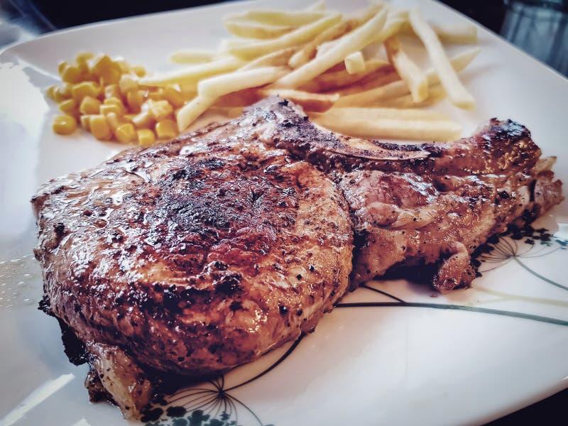 Varkensvleeslapje vlees met frieten op witte plaat stock fotografie