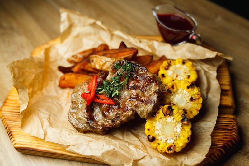 Varkensvleeslapje vlees met geroosterd graan en aardappels in creool royalty-vrije stock afbeelding