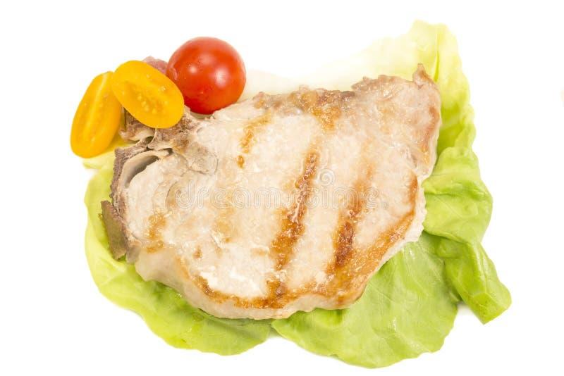 Varkensvleeslapje vlees op wit wordt ge?soleerd dat royalty-vrije stock afbeelding
