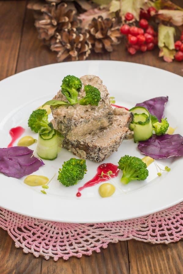 Varkensvleesmedaillons in micro- greens van de roomsaus en op een witte plaat Houten achtergrond Hoogste mening Close-up stock afbeeldingen