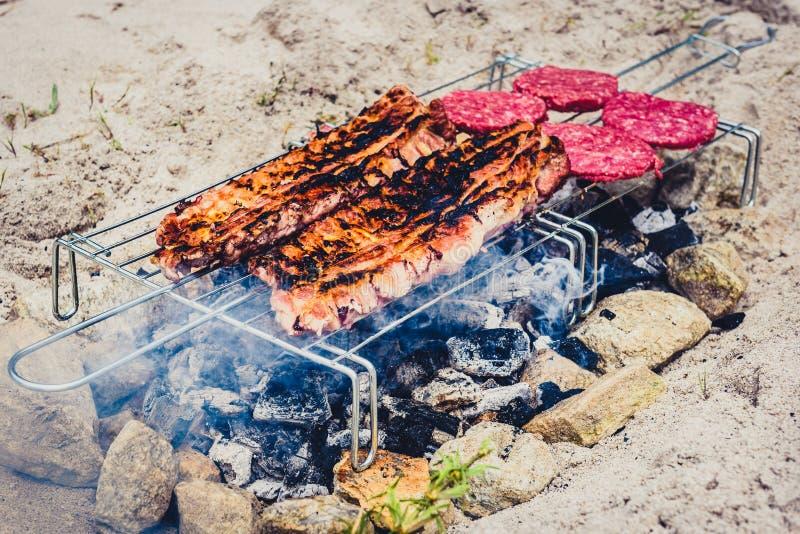 Varkensvleesribben en burgers bij de eigengemaakte geïmproviseerde BBQ barbecuegrill royalty-vrije stock foto