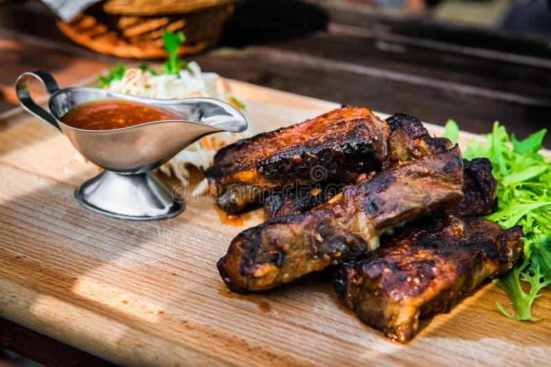 Varkensvleesribben met saus en salade op houten bureau bij het restaurant royalty-vrije stock afbeelding