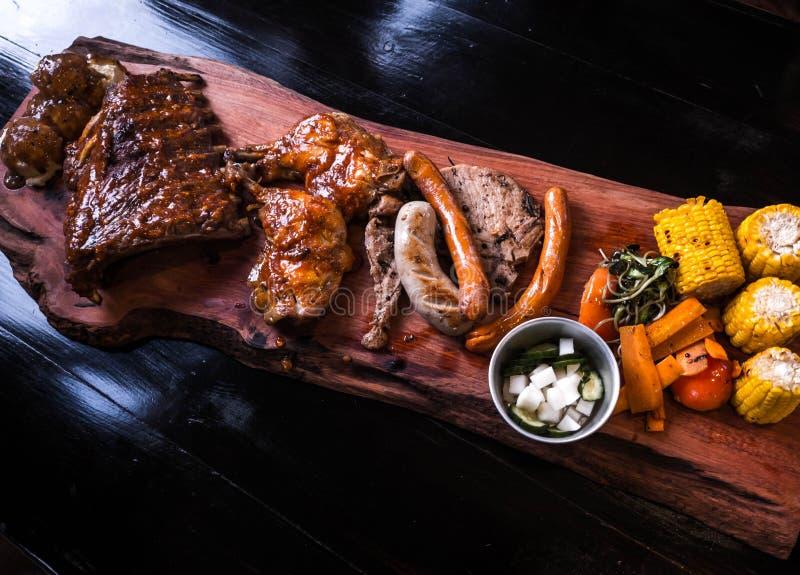 Varkensvleesribben, worsten, varkenskoteletten en geroosterde kip op een houten dienblad stock afbeeldingen