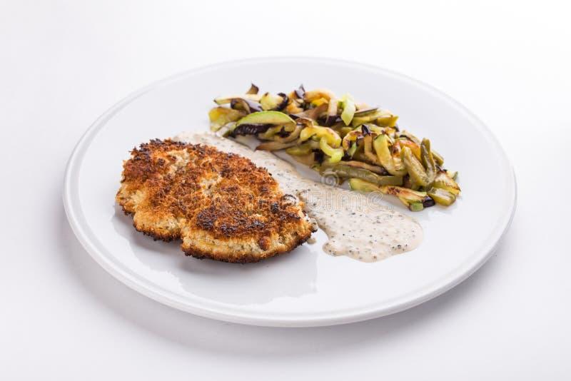 Varkensvleesschnitzel met gebraden die aardappels en paddestoelen en witte saus op witte achtergrond wordt geïsoleerd stock afbeelding