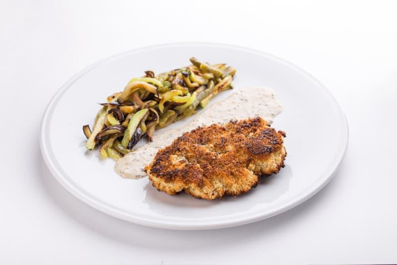 Varkensvleesschnitzel met gebraden die aardappels en paddestoelen en witte saus op witte achtergrond wordt geïsoleerd royalty-vrije stock foto