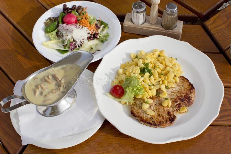 Varkensvleestenderlion op plaat met Spätzle wordt gediend en de champignons mengden salade en saus die stock foto's