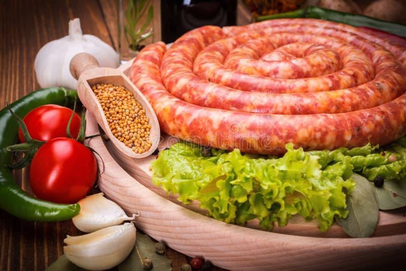Varkensvleesworst langs groenten en kruiden royalty-vrije stock afbeeldingen