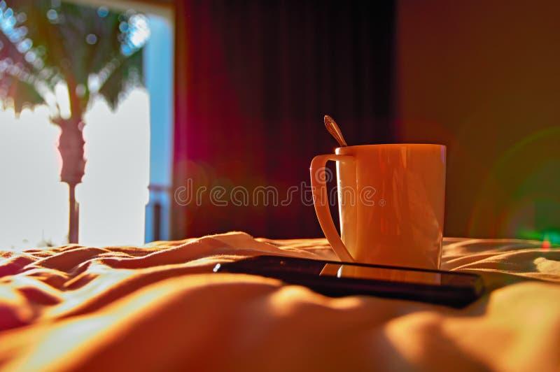 Varm afton för begrepp i hemtrevligt rum Solnedgångsolen exponerar rånar och mobiltelefonen på sängen kopiera avstånd royaltyfri bild