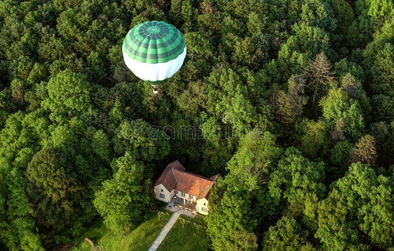 Varm ballong över hus och skog fotografering för bildbyråer