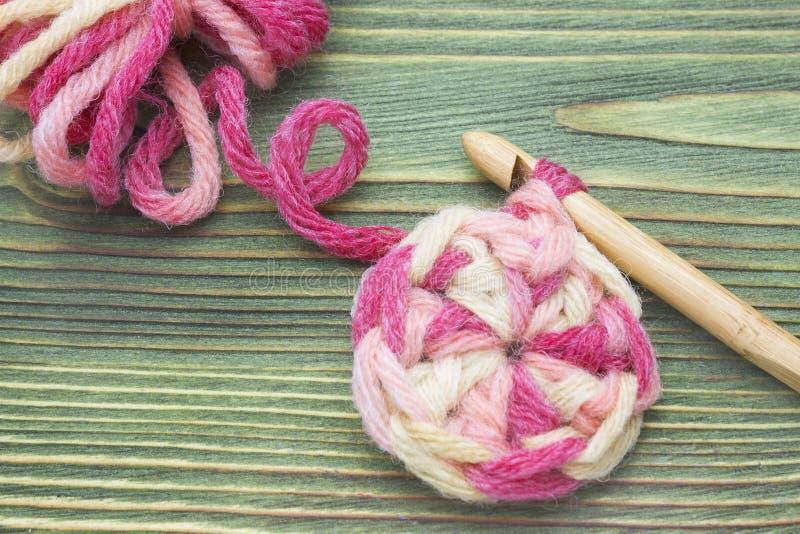 Varm boll för rosa färgvintergarn för att sticka och virkning på tabellen Closeupfoto av virkningdoilyen Lantlig virkningtråd och royaltyfri bild