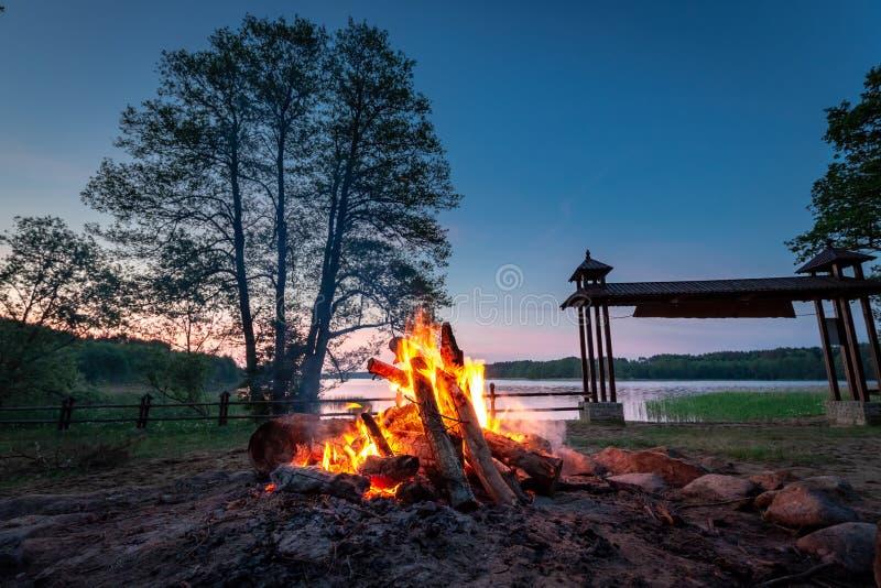 Varm brasa på skymning vid sjön i sommar arkivfoto