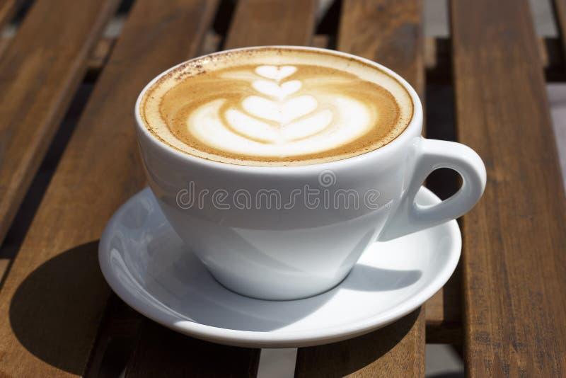 Varm cappuccino med fradga och modellen på träbakgrund, sidosikt arkivbild