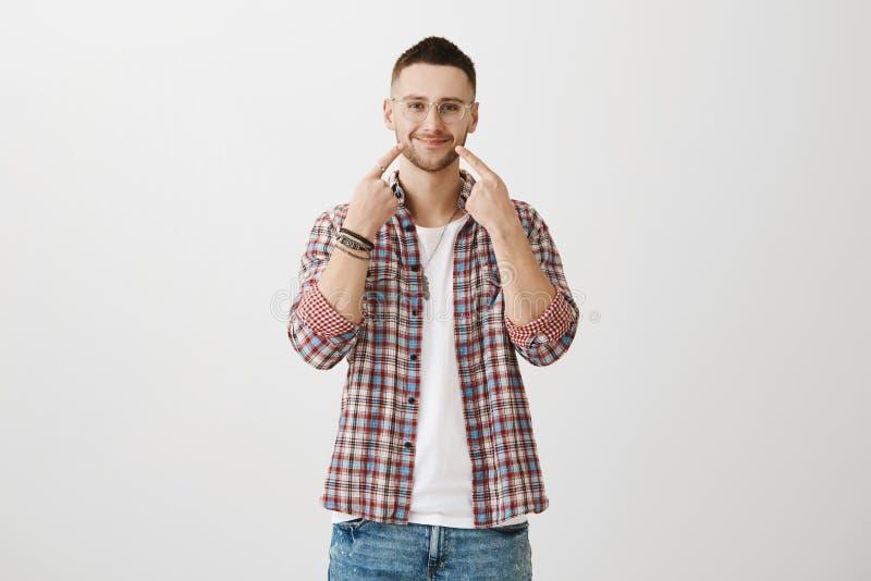 Varm caucasian man med borstet, bärande moderiktiga exponeringsglas och dräkten som sträcker leende och pekar på munnen med index arkivfoto