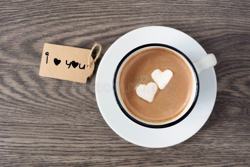 Varm choklad med hjärta formade marshmallower och jag älskar dig etiketten royaltyfria foton