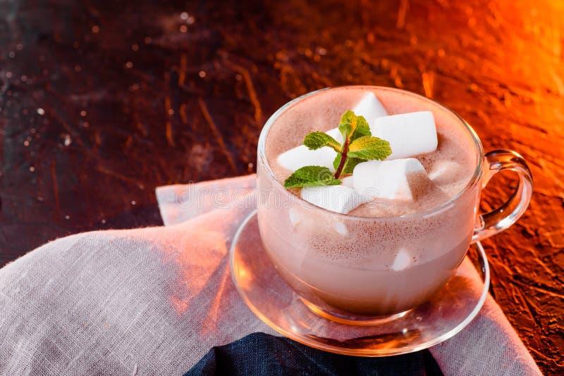 Varm choklad med marshmallower i en exponeringsglaskopp med mintkaramellen kakao Orange ljus för solnedgång arkivfoto