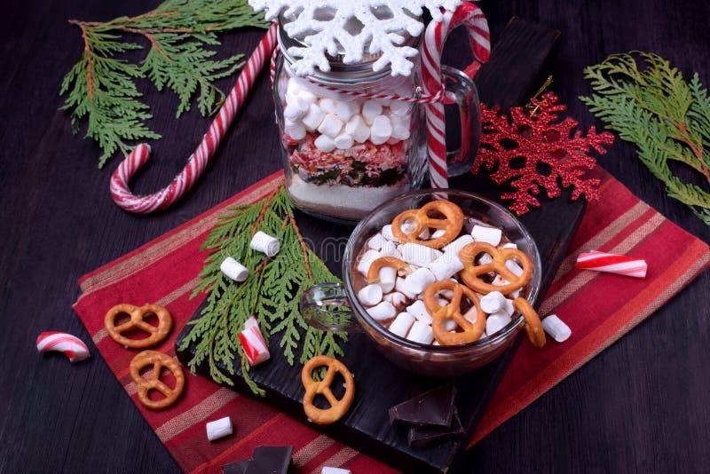 Varm choklad med marshmallower och kringlor i en kopp och en torr blandning för att förbereda drinken arkivfoto