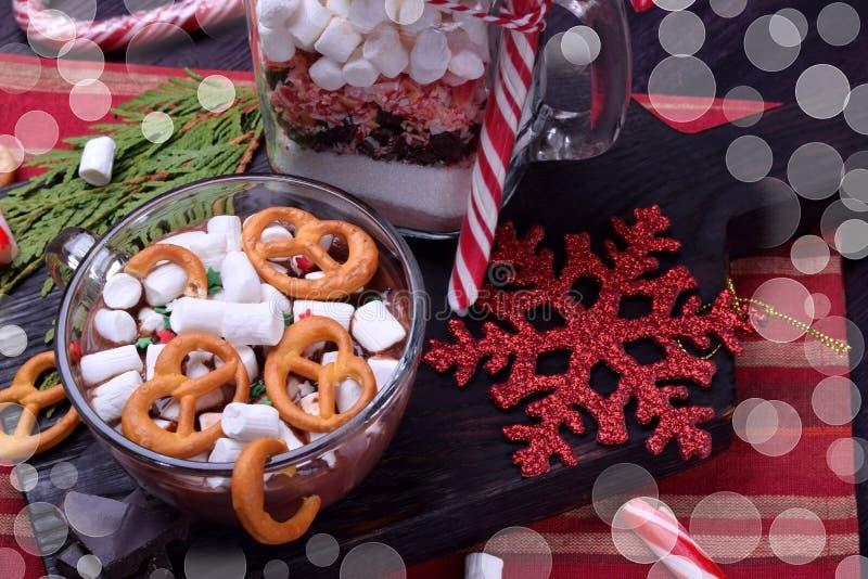 Varm choklad med marshmallower och kringlor i en kopp och en torr blandning för att förbereda drinken royaltyfri foto