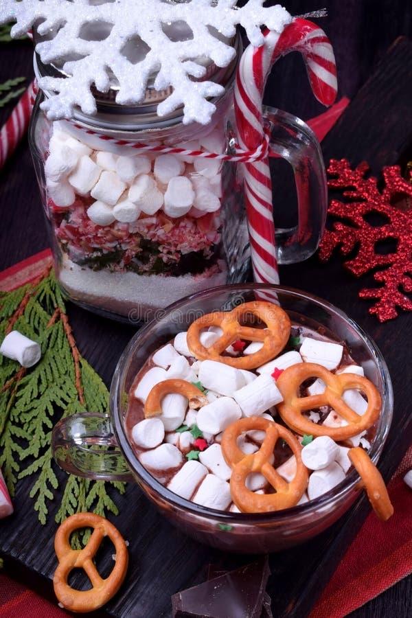 Varm choklad med marshmallower och kringlor i en kopp och en torr blandning för att förbereda drinken arkivbilder
