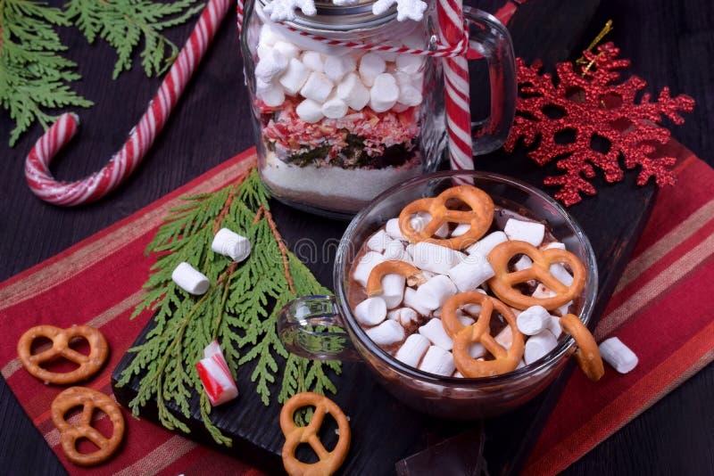 Varm choklad med marshmallower och kringlor i en kopp och en torr blandning f?r att f?rbereda drinken arkivbilder