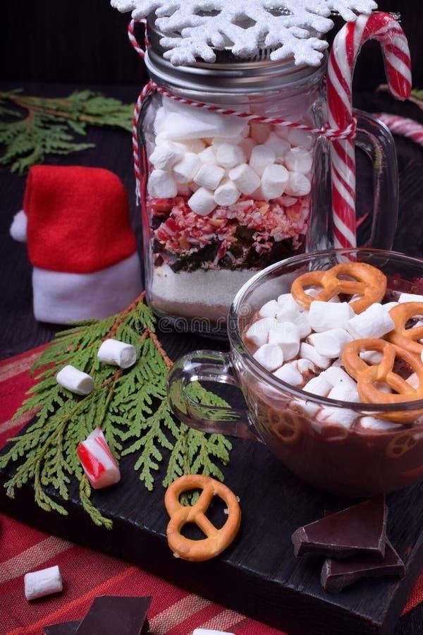 Varm choklad med marshmallower och kringlor i en kopp och en torr blandning f?r att f?rbereda drinken arkivfoto