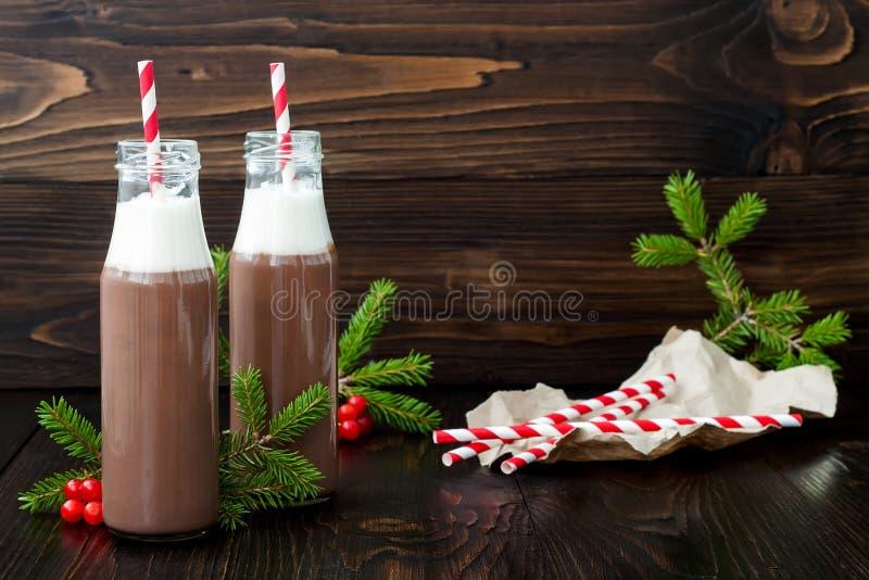 Varm choklad med piskad kräm i gammalmodiga retro flaskor med röda randiga sugrör Julferiedrink Kopia s för fri text royaltyfri bild