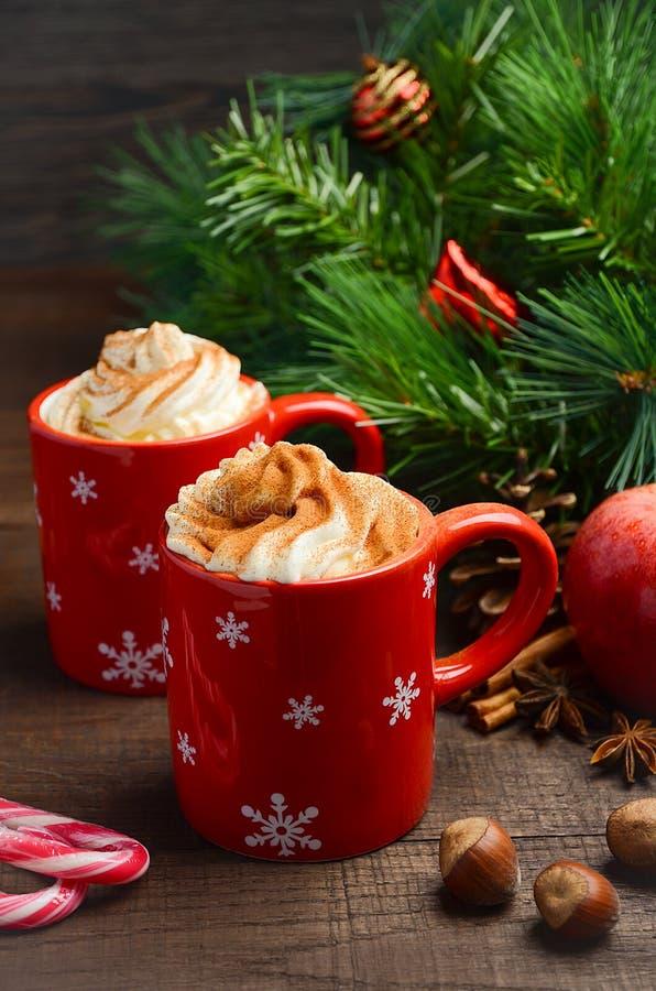 Varm choklad med piskad kräm i röda koppar för julsammansättning för bauble blått exponeringsglas royaltyfri fotografi