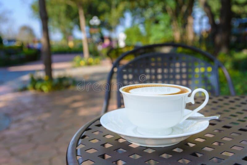 Varm coffe i en vit kopp med utomhus- sikt royaltyfria foton